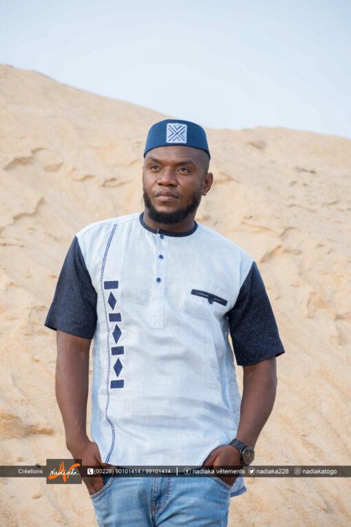 Homme portant une chemise brodée Nadiaka bleu au bord de la plage