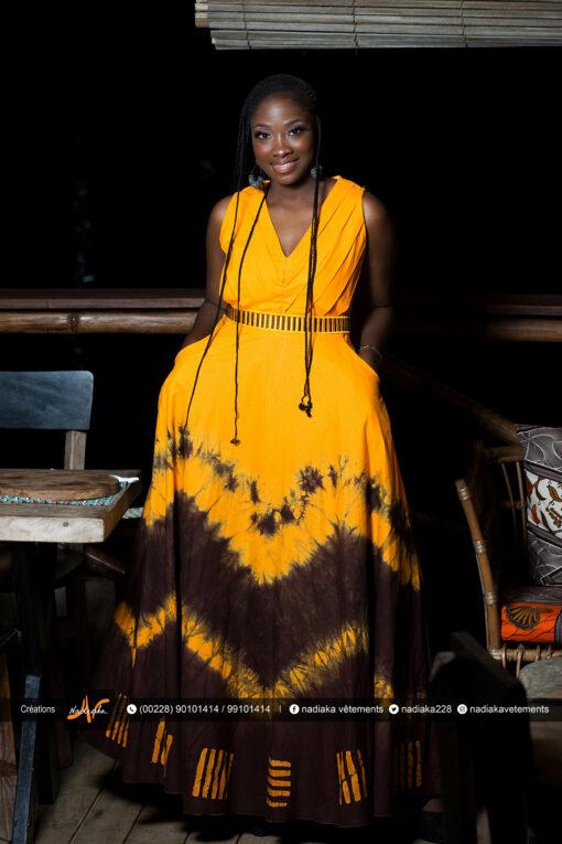 """Robe longue brodée """"Adétèdou séwloué"""", tissu batik tons orange et marron, ceinture brodée assortie."""